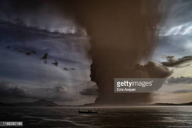 A fishing boat sails along a lake as Taal Volcano erupts on January 12 2020 in Talisay Batangas province Philippines Local authorities have begun...