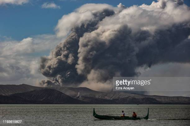 A fishing boat sails along a lake as Taal Volcano erupts on January 14 2020 in Talisay Batangas province Philippines The Philippine Institute of...