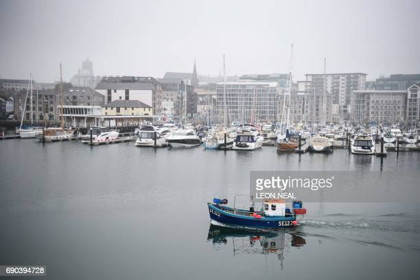 A fishing boat sails from the harbour as Britain's Prime Minister Theresa May attends a general election campaign visit to Plymouth fisheries in...
