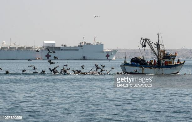 A fishing boat sails near the United States Navy hospital ship USNS Confort anchored off the port of Paita in Piura region northern Peru on November...
