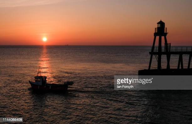 A fishing boat sails out of Whitby Harbour as the sun rises on Easter Sunday on April 21 2019 in Whitby United KingdomThis Easter weekend has broken...