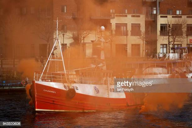 A fishing boat sails through red smoke as fishermen take part in a nationwide protest against the Brexit transition deal on April 8 2018 in Newcastle...