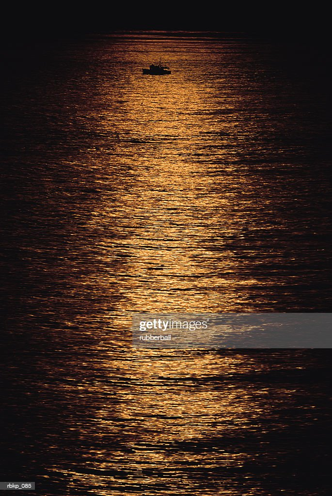 Fishing boat silhouetted against the sea, reflecting the last rays of sunlight on its surface : Stockfoto