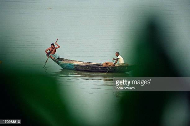 Fishing boat through leaves river Hooghly West Bengal India