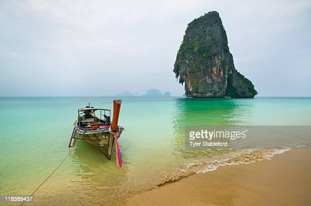 Fishing boat tied on a beach near limestone cliff.