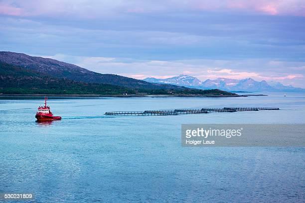Fishing boat tows salmon farm enclosures