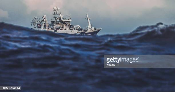 fishing boat trawler sailing out at rough sea - fishing boat stock pictures, royalty-free photos & images