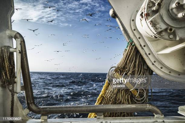 fishing boat trawler sailing out at rough sea - italy vs norwegian stock pictures, royalty-free photos & images