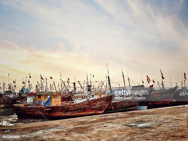 Fishing Boats And Boathouses Against Sky