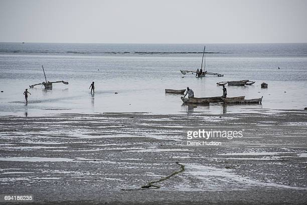 Fishing boats and dugout canoes some with outriggers and sail powered seen here grounded on the beach at low tide The small fishing town and...