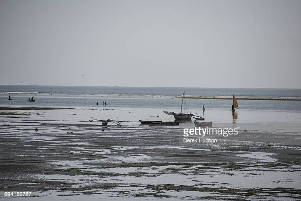 Fishing boats and dugout canoes, some with outriggers and sail powered seen here grounded on the beach at low tide .The small fishing town and...