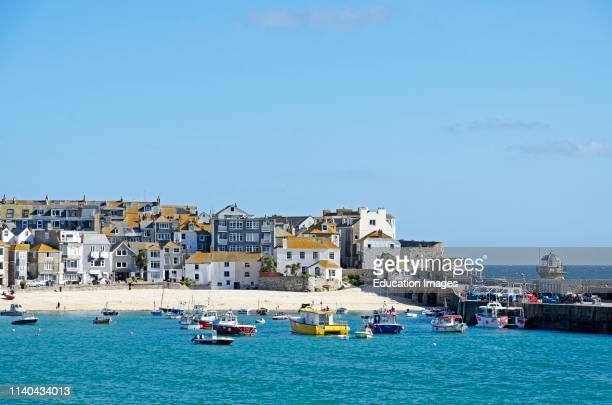 fishing boats and holiday homes apartments harbor Cornwall England Britain uk