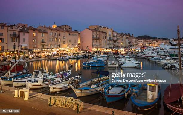 Fishing boats and luxury yachts in the port of St Tropez at sunset, Provence, France