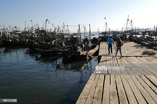 Fishing boats are berthed in a fishing village at Dalian Bay port in Dalian northeast China's Liaoning province on May 20 after North Koreans...