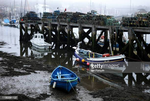 Fishing boats are tied up at low tide as sea fog shrouds Whitby Harbour on May 18 2019 in Whitby England Heavy fog and mist covered many parts of the...