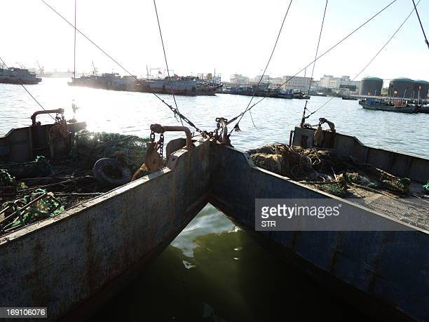 Fishing boats berth in a fishing village at Dalian Bay fishing port in Dalian northeast China's Liaoning province on May 20 2013 China has called on...