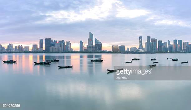 fishing boats floating on qiantang river against qianjiang new town cbd, hangzhou,china - hangzhou stock photos and pictures