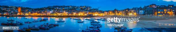 Fishing boats harbour beside warm village lights St Ives Cornwall