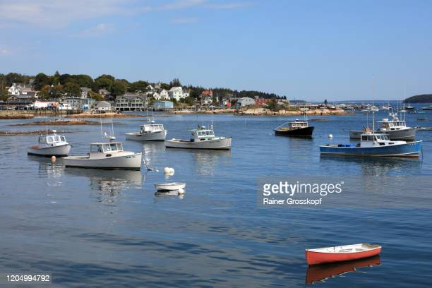 fishing boats in a tranquil bay of a small fishing town on the atlantic coast in maine - rainer grosskopf stock-fotos und bilder