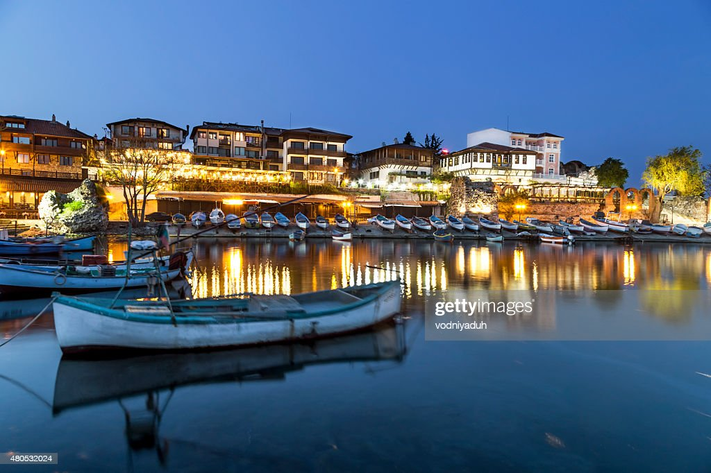Fishing boats in costal city at night : Stock Photo