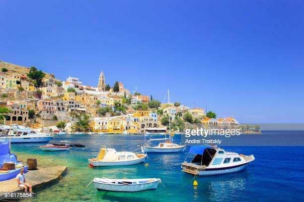 fishing boats in symi harbour, greece - greece stock pictures, royalty-free photos & images