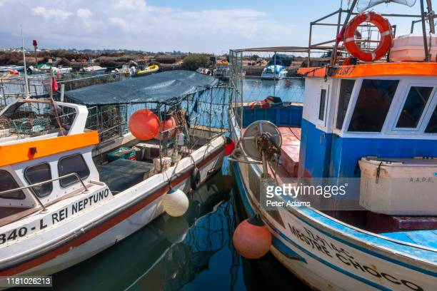 fuseta, portugal - april 2019: fishing boats in the harbour of fuseta, algave, portugal - moored stock pictures, royalty-free photos & images
