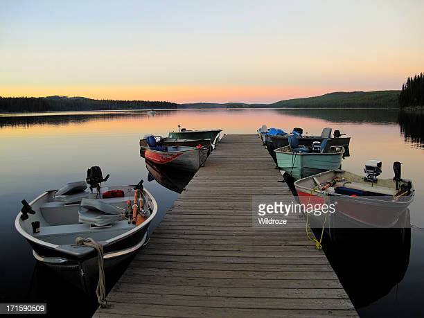 Fishing boats line dock at sunset