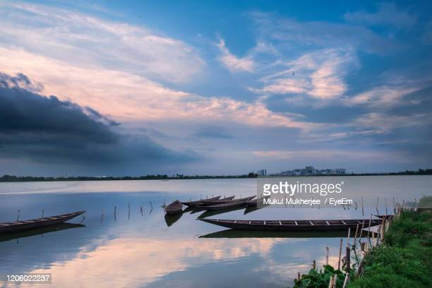 fishing boats moored in lake against sky - west bengal stock pictures, royalty-free photos & images