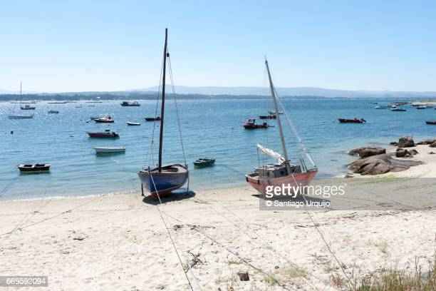 fishing boats moored on a beach - pontevedra province stock photos and pictures