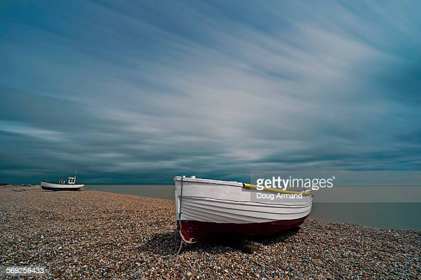 fishing boats on a pebble beach under stormy skies - dungeness stock pictures, royalty-free photos & images