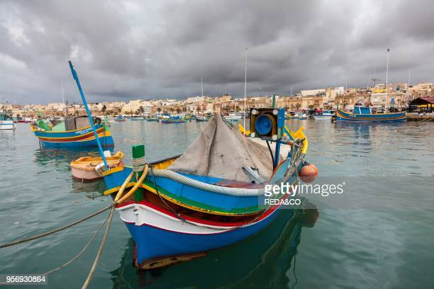 Fishing boats on the harbour of Marsaxlokk The colorfull traditional fishing boats are called Luzzu and have a painted eye on the bow. Called eye of...