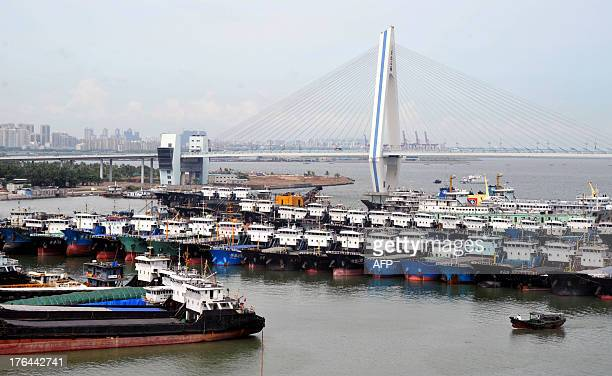 Fishing boats return from the sea and berth in a port in Haikou, south China's Hainan province, as powerful Typhoon Utor approaches the area on...