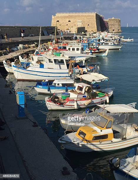 Fishing boats stand near a Venetian fortress in the main harbour on August 22 2015 in Heraklion Greece Crete is a popular summer tourist destination