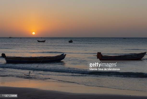Fishing boats stuck in the sand, on the edge of Jericoacoara beach, at sunset.