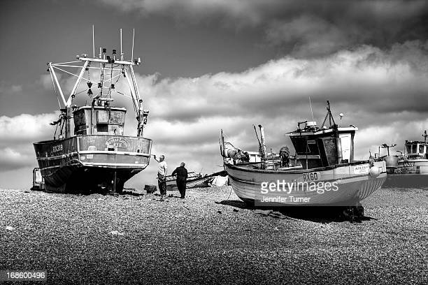 CONTENT] Fishing boats with fishermen on the beach at Hastings East Sussex in 2012 Black and white image