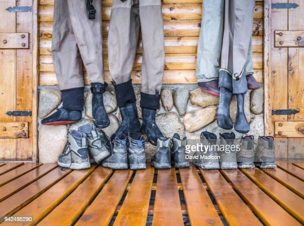 fishing boots and waders in lodge - waders stock pictures, royalty-free photos & images