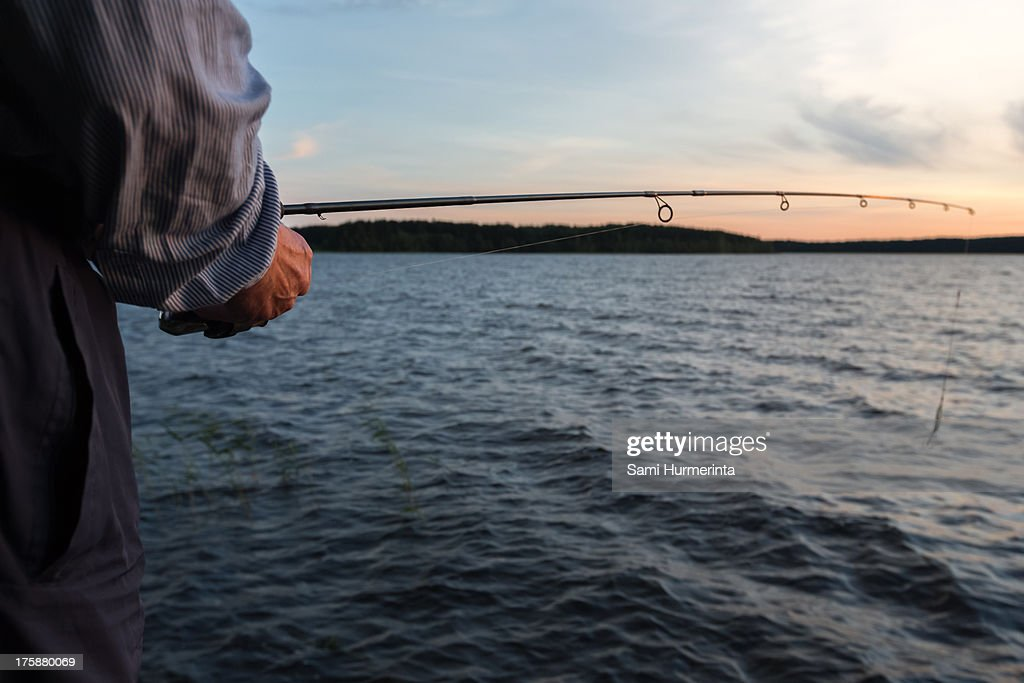 Fishing by the lake at sunset : Stock Photo