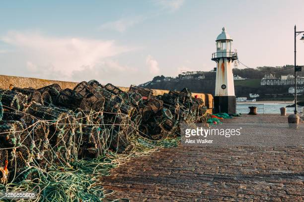 fishing equipment on harbour wall with lighthouse - st. ives cornwall stock pictures, royalty-free photos & images