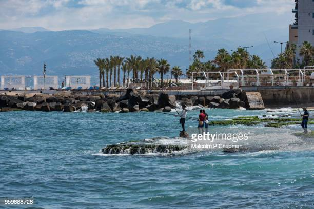 fishing from rocks on the corniche, beirut, lebanon - beirut stock pictures, royalty-free photos & images