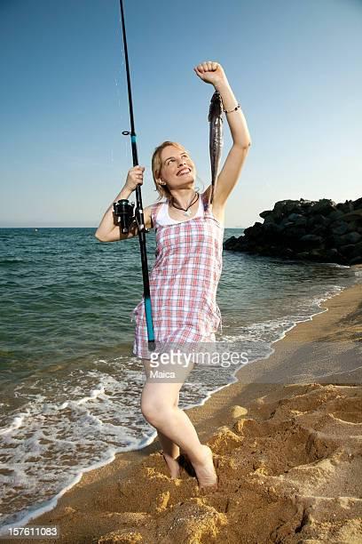 pesca chica con su pesca en la playa - merluza fotografías e imágenes de stock