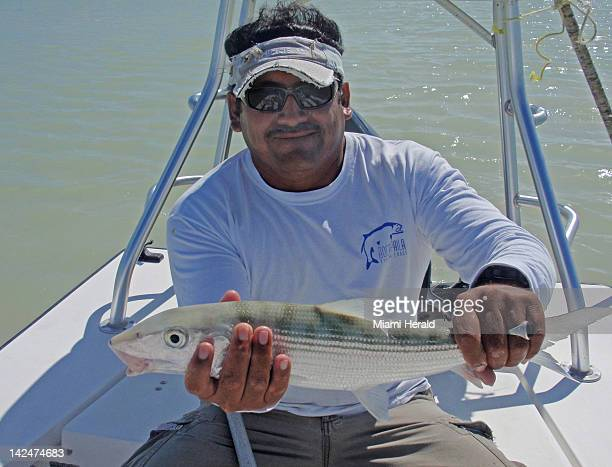 Fishing guide Jorge Luciano holds up a bonefish caught in Boca Paila Lagoon in Mexico's southern Yucatan region