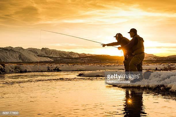 Apuntando pesca de trucha fuera una guía en puesta de sol