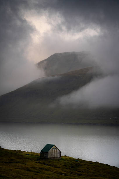 Fishing hut by sea and mountains in fog, Fuglafjordur, Faeroe Islands