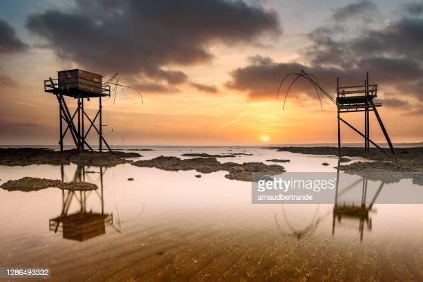fishing huts on beach at low tide at sunset, saint-michel-chef-chef, loire-atlantique, france - loire atlantique photos et images de collection