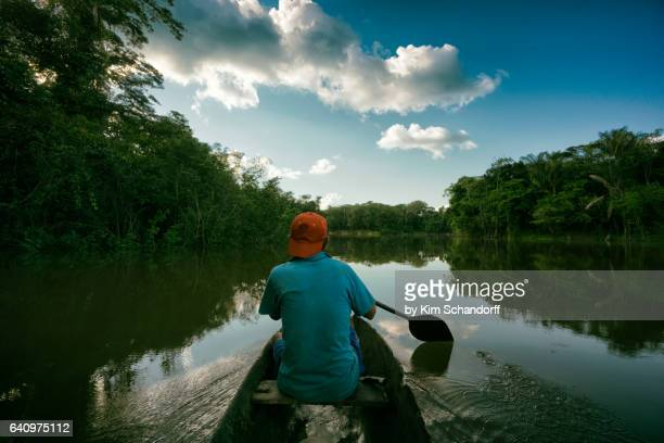 fishing in a small canoe on river maniti - iquitos stock pictures, royalty-free photos & images