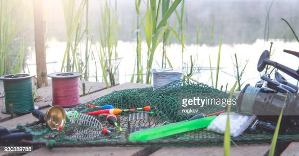 fishing lures on the river bank, in the background of the rising sun. - fly casting stock pictures, royalty-free photos & images