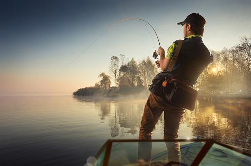 Fishing. Man fishing on a lake on boat 898140606