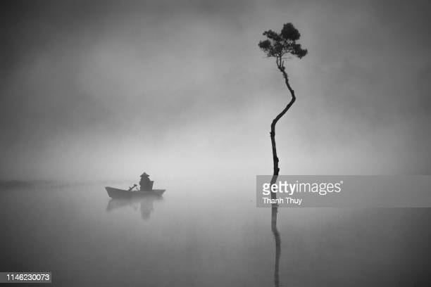 Fishing man on the fishing boat on the misty lake