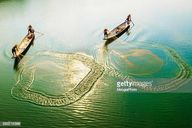 Fishing men on boat in river in Hue, Vietnam.