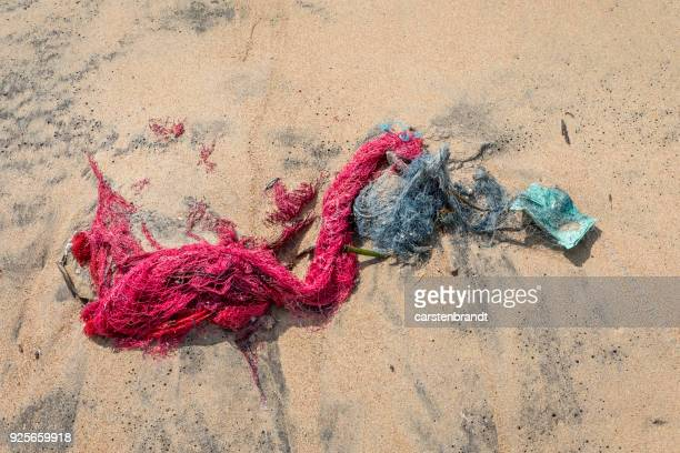 fishing net and garbage on the beach - sri lanka garbage stock photos and pictures